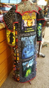 A multi-paneled quilted coat made from themed t-shirts on a display dummy.