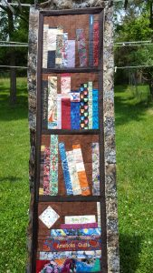 Quilted wall hanging made to look like a bookcase filled with books and other objects against a natural outdoor background.